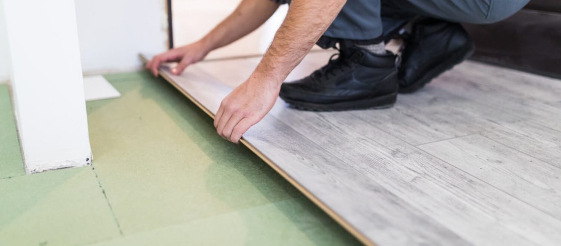 worker-processing-floor-with-laminated-flooring-boards-1